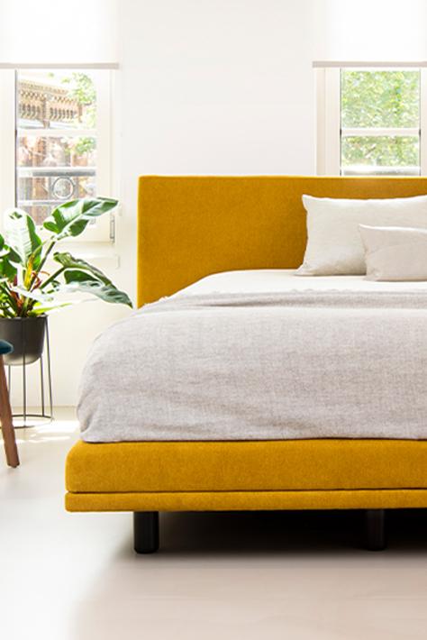 Meesterlyk boxspring in gele bekleding met slank frame van Bed habits